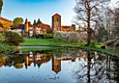 LITTLE MALVERN COURT, WORCESTERSHIRE: THE COURT AND LITTLE MALVERN PRIORY REFLECTED IN LAKE, SPRING, LAKES, WATER, PONDS, POOLS, REFLECTIONS, MAGNOLIA X SOULANGEANA ALBA SUPERBA