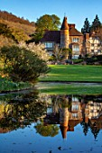 LITTLE MALVERN COURT, WORCESTERSHIRE: THE COURT REFLECTED IN LAKE, SPRING, LAKES, WATER, PONDS, POOLS, REFLECTIONS, MAGNOLIA X SOULANGEANA ALBA SUPERBA
