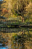LITTLE MALVERN COURT, WORCESTERSHIRE: WOODEN BRIDGE REFLECTED IN THE LAKE, POND, WATER, POOLS, SPRING