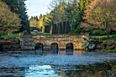 THENFORD GARDENS & ARBORETUM, NORTHAMPTONSHIRE: LAKE, BRIDGE, GUNNERA SCULPTURE, YEWS, SPRING