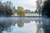 THENFORD GARDENS & ARBORETUM, NORTHAMPTONSHIRE: THE LAKE AND HOUSE WITH WILLOW TREE, MORNING, MIST, SPRING