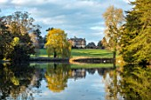 THENFORD GARDENS & ARBORETUM, NORTHAMPTONSHIRE: VIEW OF THE HOUSE FROM THE LAKE IN SPRING