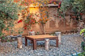 TAROUDANT, MOROCCO: DESIGNERS ARNAUD MAURIERES AND ERIC OSSART: WOODEN TABLE AND CHAIRS, MUD WALL, BOUGAINVILLEA, CLIMBERS, ARID, DRY, GRAVEL