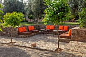 TAROUDANT, MOROCCO: DESIGNERS ARNAUD MAURIERES AND ERIC OSSART: TERRACE, SEATING AREA, TABLES, CHAIRS, LOUNGERS, ORANGE CUSHIONS