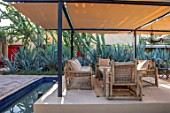 TAROUDANT, MOROCCO: DESIGNERS ARNAUD MAURIERES AND ERIC OSSART: BED OF AGAVES, SUCCULENTS, DRY, ARID, GARDENS, SEATING AREA, CANOPY, AWNING, RILL, WATER, TABLE, CHAIRS