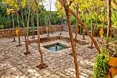 TAROUDANT, MOROCCO: DESIGNERS ARNAUD MAURIERES AND ERIC OSSART: RECTANGULAR GARDEN, WATER, POND, POOL, FOUNTAIN, PATIO, PAVING, GREEN BENCHES, SEATS, ACACIA TREES, SHADE, SHADY
