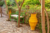 TAROUDANT, MOROCCO: DESIGNERS ARNAUD MAURIERES AND ERIC OSSART: SUNKEN PATIO, PAVING, GREEN BENCHES, SEATS, ACACIA TREES, SHADE, SHADY, YELLOW, TERRACOTTA, CONTAINERS