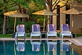 TAROUDANT, MOROCCO: DESIGNERS ARNAUD MAURIERES AND ERIC OSSART: SWIMMING POOL, WATER, SUNLOUNGERS, TOWELS, CANOPY, SUN LOUNGERS, PURPLE, BLUE