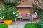 TAROUDANT, MOROCCO: DESIGNERS ARNAUD MAURIERES AND ERIC OSSART: COVERED SEATING AREA WITH CHAIRS, TABLE AND SWING SEAT. AWNINGS, CANOPY, CANOPIES, YELLOW CONTAINER WITH OLEANDER