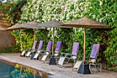 TAROUDANT, MOROCCO: DESIGNERS ARNAUD MAURIERES AND ERIC OSSART: SWIMMING POOL, DECKCHAIRS, DECK CHAIRS, PURPLE TOWELLS, SHADES, SHADY, BOUGAINVILLEA, HEDGES, HEDGING