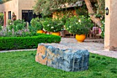 TAROUDANT, MOROCCO: DESIGNERS ARNAUD MAURIERES AND ERIC OSSART: GARDEN WITH GRASS, LAWN, ROCK, ROCKS, TERRACE, GLAZED YELLOW CONTAINERS, OLEANDERS