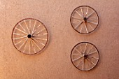 TAROUDANT, MOROCCO: DESIGNERS ARNAUD MAURIERES AND ERIC OSSART: OLD CART WHEELS ON MUD WALL AT ENTRANCE TO THE GARDEN