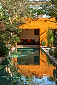 TAROUDANT, MOROCCO: DESIGNERS ARNAUD MAURIERES AND ERIC OSSART: DAR AL HOSSOUN - EXOTIC PLANTING, POOL, WATER, CANAL, LOGGIA, ORANGE, CUSHIONS, SEATING