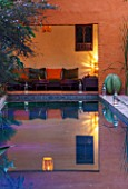 TAROUDANT, MOROCCO: DESIGNERS ARNAUD MAURIERES AND ERIC OSSART: DAR AL HOSSOUN - EXOTIC PLANTING, POOL, WATER, CANAL, LOGGIA, ORANGE, CUSHIONS, SEATING, LIGHTING, EVENING, NIGHT