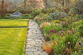 GRAVETYE MANOR SUSSEX: SPRING, APRIL, COUNTRY, GARDEN, LUTYENS BENCH, SEAT ON LAWN, PATHS AND BORDER FILLED WITH TULIPS