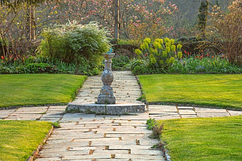 GRAVETYE_MANOR_SUSSEX_SPRING_APRIL_COUNTRY_GARDEN_LUTYENS_BENCH_SEAT_ON_LAWN_PATHS_AND_STONE_SUNDIAL