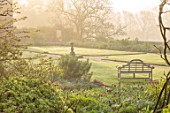 GRAVETYE MANOR SUSSEX: SPRING, APRIL, COUNTRY, GARDEN, PATH, LAWN, STONE SUNDIAL, MIST, MISTY, BORDERS, TULIPS, LUTYENS BENCH, SEAT