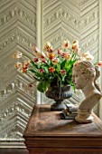 THE LAND GARDENERS, WARDINGTON MANOR, OXFORDSHIRE: TULIPS ARRANGED IN METAL CONTAINER ON WOODEN TABLE. STATUE, SPRING, ARRANGEMENT, CUTTING