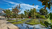 RADICEPURA GARDEN FESTIVAL, SICILY, ITALY: HOME GROUND BY ANTONIO PERAZZI. WATER GARDEN WITH TREES, WATER FEATURE, PALM TREES
