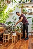 JAMIES JUNGLE, LONDON HOUSE OF JAMIE SONG: APARTMENT FILLED WITH HOUSEPLANTS. INDOORS, GREEN INTERIORS,  JAMIE SONG WATERING