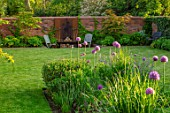 DESIGNER JAMES SCOTT, THE GARDEN COMPANY: LAWN, MEADOW SQUARE WITH ALLIUM VIOLET BEAUTY, LAWN,  WOODEN CHAIRS, WALL, RUSTY METAL WALL ORNAMAMENT, MAY, SPRING