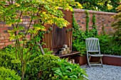 DESIGNER JAMES SCOTT, THE GARDEN COMPANY: BARBEQUE, WOODEN CHAIRS, WALL, RUSTY METAL WALL ORNAMAMENT, MAY, SPRING, ALLIUMS, GRAVEL