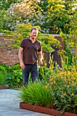 DESIGNER JAMES SCOTT, THE GARDEN COMPANY: JAMES SCOTT INHIS GARDEN BESIDE BED WITH GEUM TOTALLY TANGERINE