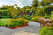 DESIGNER JAMES SCOTT, THE GARDEN COMPANY: STONE TERRACE, PATIOS, PAVED, CORTEN STEEL EDGED BEDS, TABLE AND CHAIRS, AMELANCHIER X GRANDIFLORA ROBIN HILL