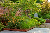 DESIGNER JAMES SCOTT, THE GARDEN COMPANY: STONE TERRACE, PATIOS, PAVED, CORTEN STEEL EDGED BEDS, GEUM TOTALLY TANGERINE, WOODEN CHAIRS, BRICK, ACER
