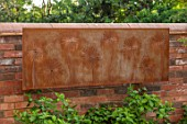 DESIGNER JAMES SCOTT, THE GARDEN COMPANY: WALL WITH CORTEN STEEL WALL PLAQUE WITH CUT OUT ALLIUMS. ORNAMENT, METAL