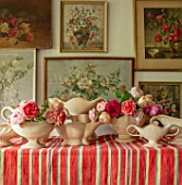 THE LAND GARDENERS, WARDINGTON MANOR, OXFORDSHIRE: CONSTANCE SPRY VASES WITH ROSES ON STRIPEY TABLECLOTH. STILL LIFE, FLOWER ROOM, CUTTING, FLOWERS