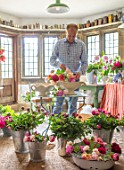 THE LAND GARDENERS, WARDINGTON MANOR, OXFORDSHIRE: CLIVE NICHOLS WITH FLOWERS IN THE FLOWER ROOM. CUTTING, CONSTANCE SPRY VASES