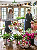 THE LAND GARDENERS, WARDINGTON MANOR, OXFORDSHIRE: BRIDGET ELWORTHY AND HENRIETTA COURTAULD IN THE FLOWER ROOM. CUTTING, CONSTANCE SPRY VASES