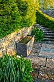 WINSON MANOR, GLOUCESTERSHIRE: PATIO, STEPS, LEAD WATER TROUGH, ZANTEDESCHIA AETHIOPICA, SUMMER, ENGLISH, COUNTRY, GARDENS