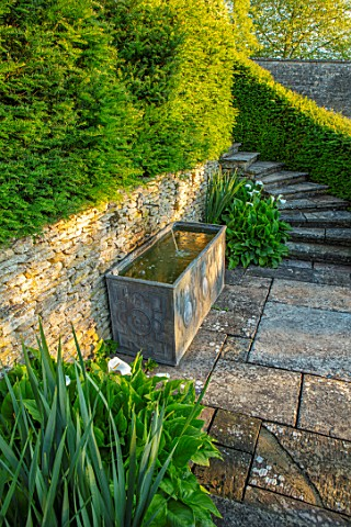 WINSON_MANOR_GLOUCESTERSHIRE_PATIO_STEPS_LEAD_WATER_TROUGH_ZANTEDESCHIA_AETHIOPICA_SUMMER_ENGLISH_CO