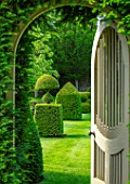 WINSON MANOR, GLOUCESTERSHIRE: VIEW THROUGH WOODEN GATE TO LAWN AND TOPIARY, CLIPPED, YEW, TAXUS, GREEN, GARDEN, SUMMER, ENGLISH, COUNTRY