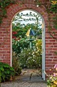 MANOR FARM, CHESHIRE: VIEW THROUGH GATE, BRICK ARCH TO BIRDFEEDER AND, TERRACE WITH CISTUS CYPRIUS, FOCAL POINT, ENGLISH, COUNTR, GARDEN, SUMMER