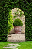 WINSON MANOR, GLOUCESTERSHIRE: LAWN, PATH, YEW HEDGES, HEDGING, GRAVEL, COURTYARD,TERRACOTTA CONTAINER, BOX BALLS, CLIPPED, TOPIARY, SUMMER, ARCH, ARCHWAY
