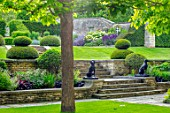 WINSON MANOR, GLOUCESTERSHIRE: LAWN, RAISED BED, YEW TOPIARY ON LAWN, CATALPA, STATUES, WALLS, SUMMER, BORDERS, STEPS