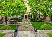WINSON MANOR, GLOUCESTERSHIRE: STEPS, CATALPAS, TERRACE, PATIO, STATUES, TABLE, CHAIRS, SUMMER, ENGLISH, COUNTRY, GARDENS