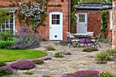 MORTON HALL, WORCESTERSHIRE: PATIO, TABLE, CHAIRS, TERRACE, PAVING, ERIGERON ANNUUS, THYMES, THYMUS SERPHYLLUM RUSSETINGS, CLEMATIS PRINCE CHARLES