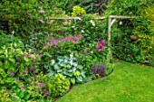 WATERDALE GARDEN, WOLVERHAMPTON, WEST MIDLANDS: LAWN AND BORDER IN SUMMER, WOODEN ARCHWAY; HOSTAS, GERANIUMS, ROSES