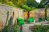THE NEWT IN SOMERSET: CORNER OF COTTAGE GARDEN IN JULY, ACANTHUS MOLLIS, PALM, GREEN WICKER SEATS, SEATING, RELAXING, WALLS