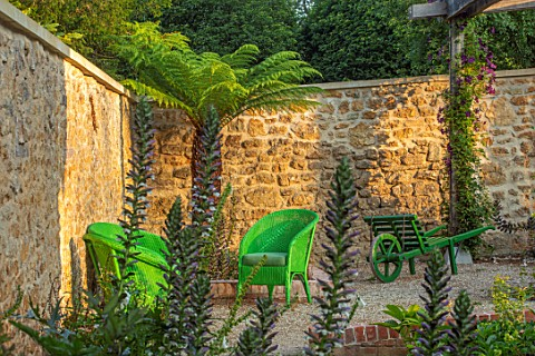 THE_NEWT_IN_SOMERSET_CORNER_OF_COTTAGE_GARDEN_IN_JULY_ACANTHUS_MOLLIS_PALM_GREEN_WICKER_SEATS_SEATIN