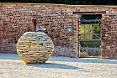THE NEWT IN SOMERSET: STONE APPLE SCULPTURE BESIDE THE MAIN GATE OF THE WALLED GARDEN. ORNAMENS