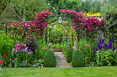 ADAMS POOL, GLOUCESTERSHIRE: LAWN, PATH, BOX BALLS, ARCHWAY, CLEMATIS MADAME JULIA CORREVON, PHLOX