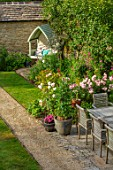 ADAMS POOL, GLOUCESTERSHIRE: VIEW FROM BEDROOM WINDOW ALONG PATH, LAWN, SWEET PEAS IN CONTAINER, TABLE AND CHAIRS, COVERED SEAT, BENCH