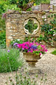 ADAMS POOL, GLOUCESTERSHIRE: HEMEROCALLIS, GRAVEL COURTYARD, STONE CONTAINER, FOLLY WALL WITH QUATREFOIL RECYCLED CHURCH WINDOW