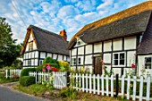 THATCH COTTAGE, WORCESTERSHIRE: THATCHED, FRONT, WHITE, PICKET FENCE, FENCING, BLACK AND WHITE COTTAGE, HOLLYHOCKS, GARDEN, ENGLISH, COTTAGES