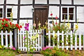 THATCH COTTAGE, WORCESTERSHIRE: THATCHED, FRONT, DOOR, GATE, WHITE, PICKET FENCE, FENCING, BLACK AND WHITE COTTAGE, HOLLYHOCKS, GARDEN, ENGLISH, COTTAGES